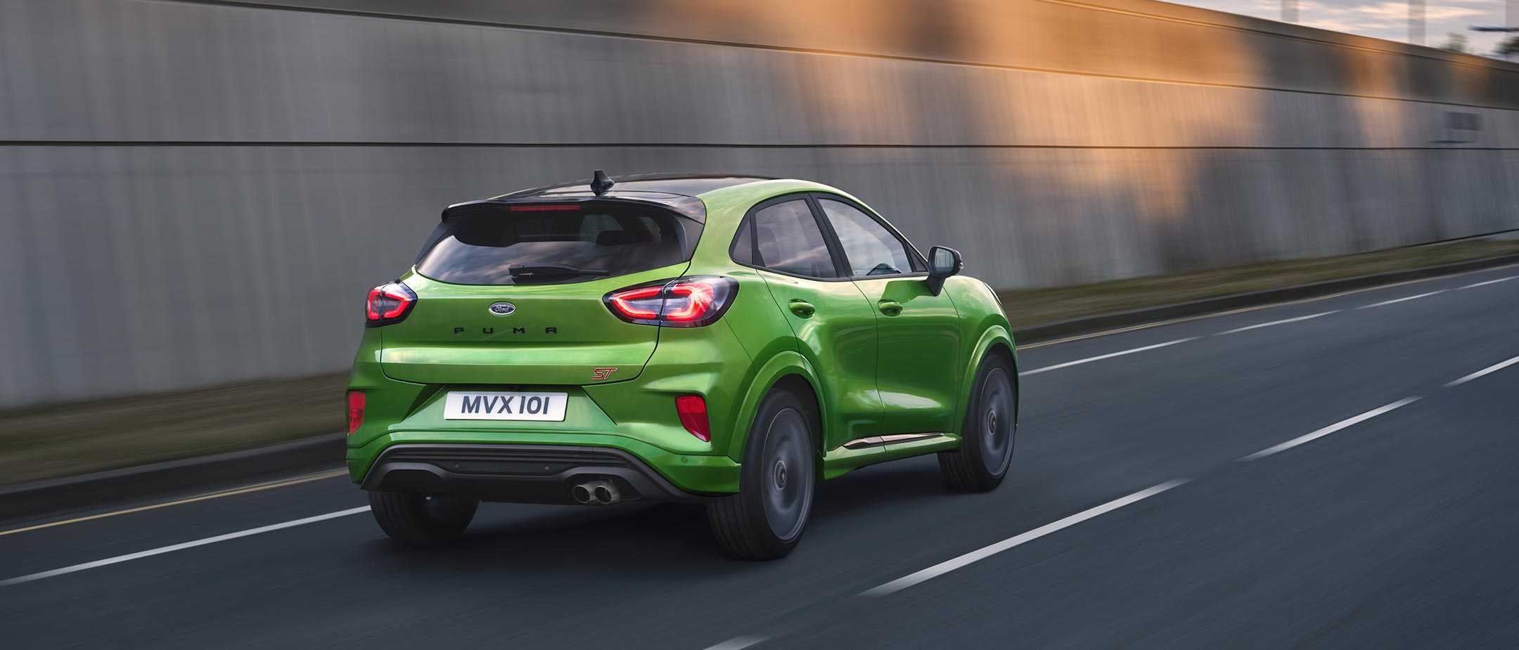 Green Ford Puma ST rear view driving on road